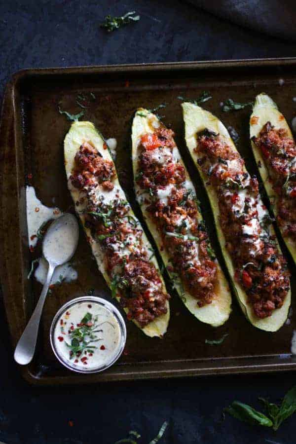 Italian-Sausage Stuffed Zucchini Boats on a sheet pan with a side of dressing