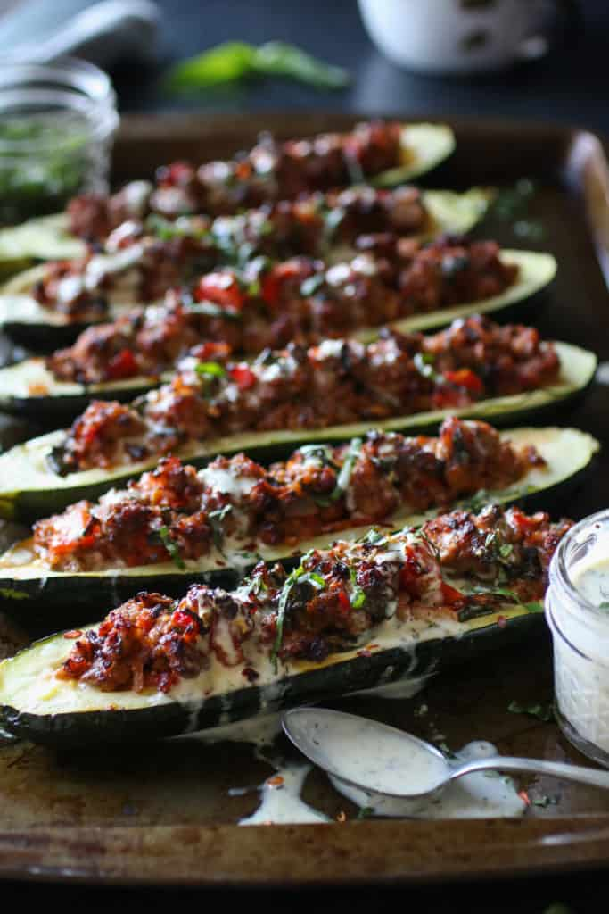 Italian sausage-stuffed Zucchini Boats on a cooking tray with a spoonful of ranch on the side