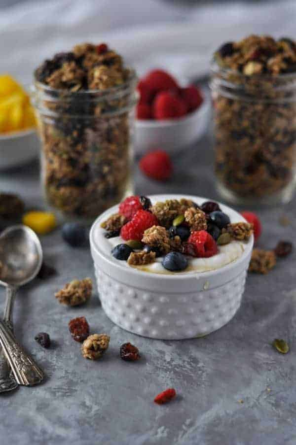 Crunchy Nut-free Paleo Granola served with yogurt, berries and a little honey in a small white bowl.