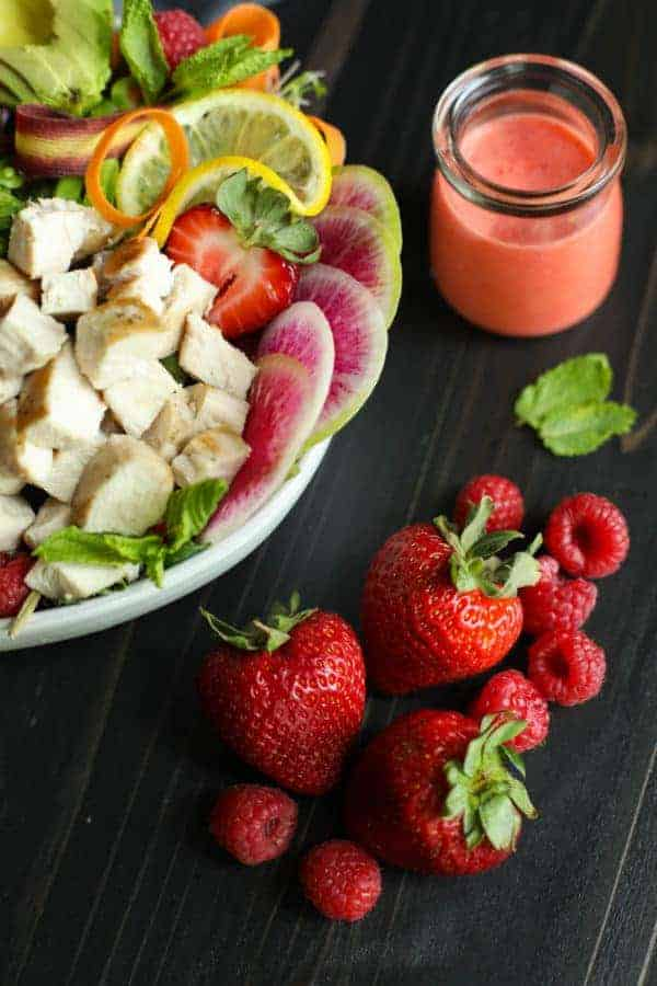 Berry Protein Salad Bowl ingredients in a white bowl with a focus on strawberries on the tabletop