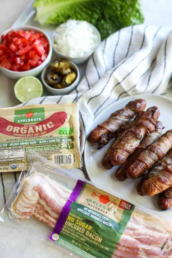 Applegate organic hot dogs and bacon packages beside a plate of bacon wrapped hot dogs