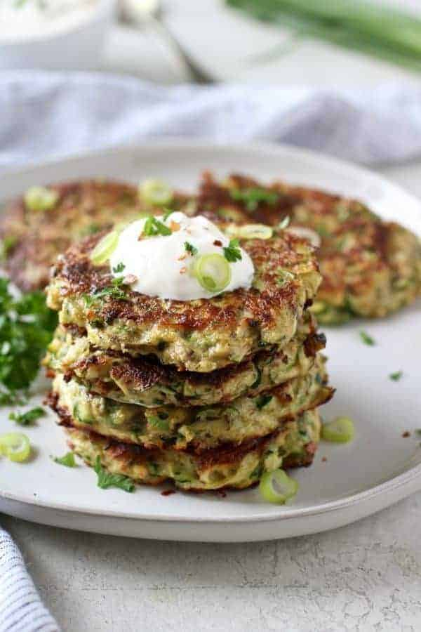 Savory Zucchini Fritters stacked on a white plate