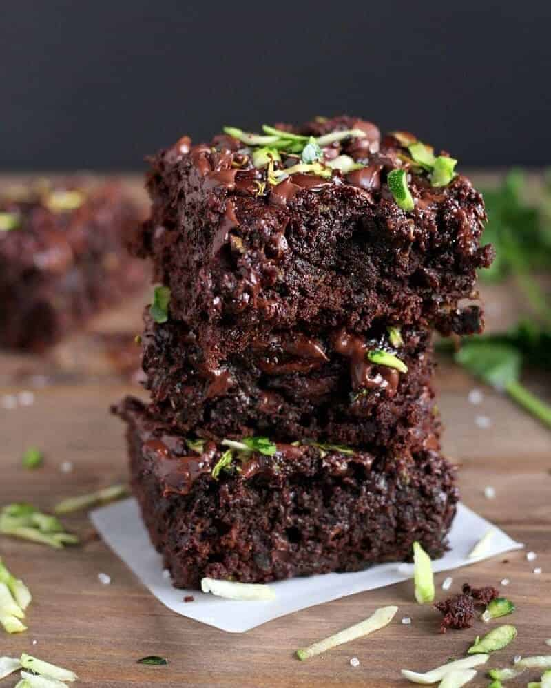 Three Healthy Double-Chocolate Zucchini Brownies stacked on a cutting board