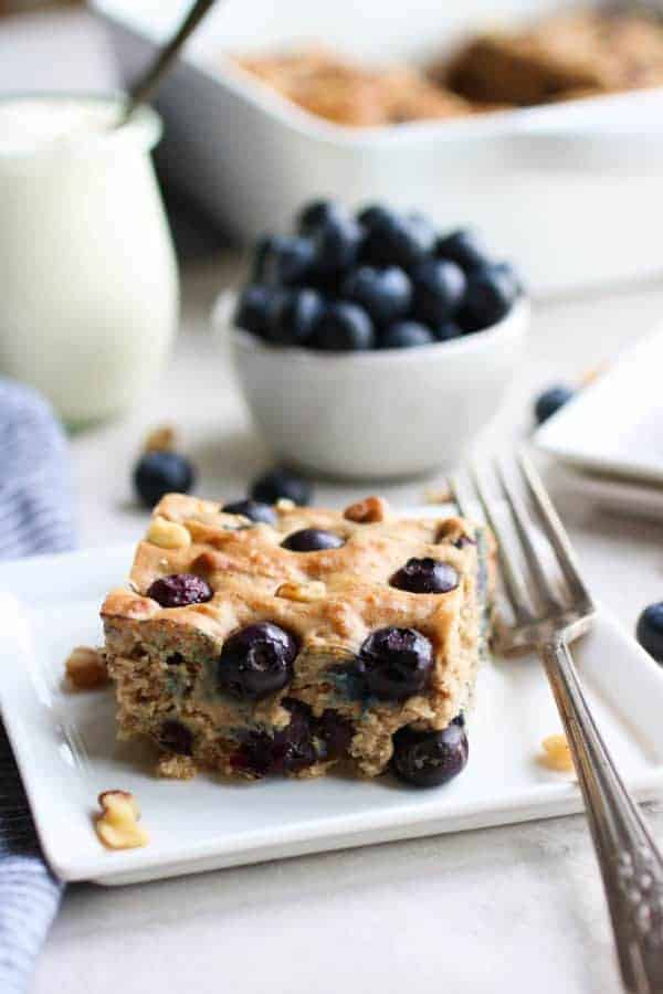 Blueberry Banana Walnut Muffin Bar on a white plate with a fork on the side and a bowl of blueberries in the distance