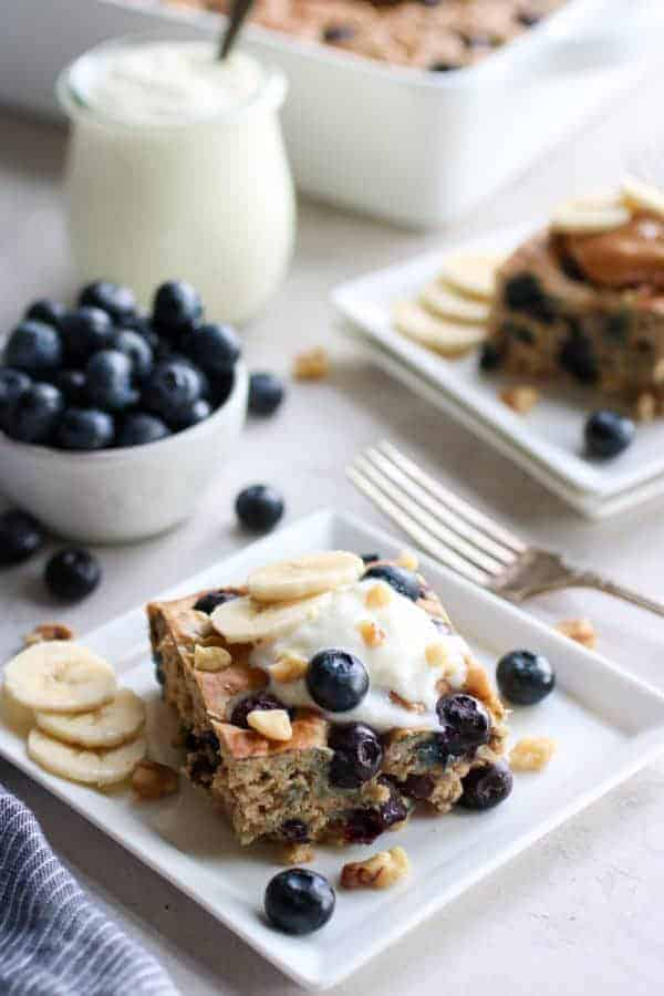 A square piece of baked oatmeal on white square plate surrounded by small bowl of blueberries, a glass cup filled with yogurt and a glimpse of the full pan as well as another plated piece