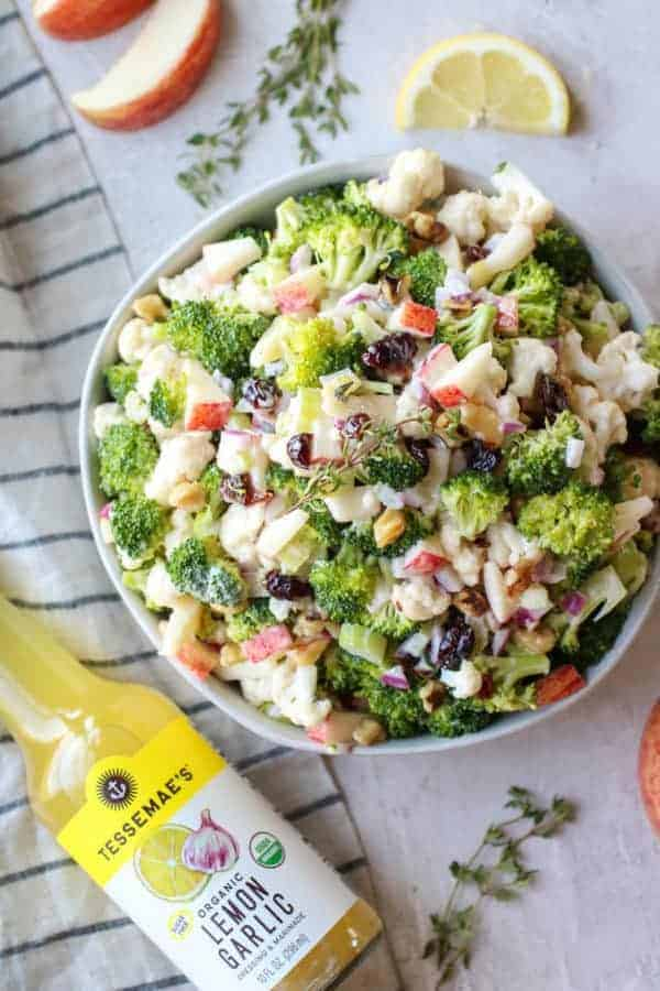 Aerial view of Apple Broccoli Cauliflower Salad in a white bowl with Tessemae's Organic Lemon Garlic Dressing & Marinade laying beside the bowl