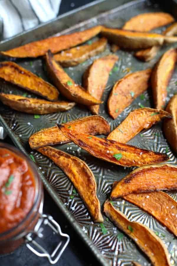Vintage baking sheet with roasted sweet potatoes sprinkled with chopped parsley and coarse sea salt.
