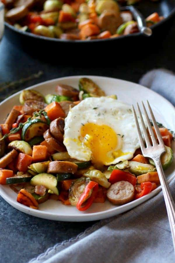 Chicken & Apple Sausage Sweet Potato Hash on a white plate with a fork