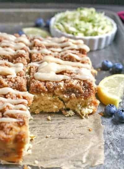 Paleo Lemon Zucchini Cake cut into squares with shredded zucchini, a lemon slice, and blueberries in the background