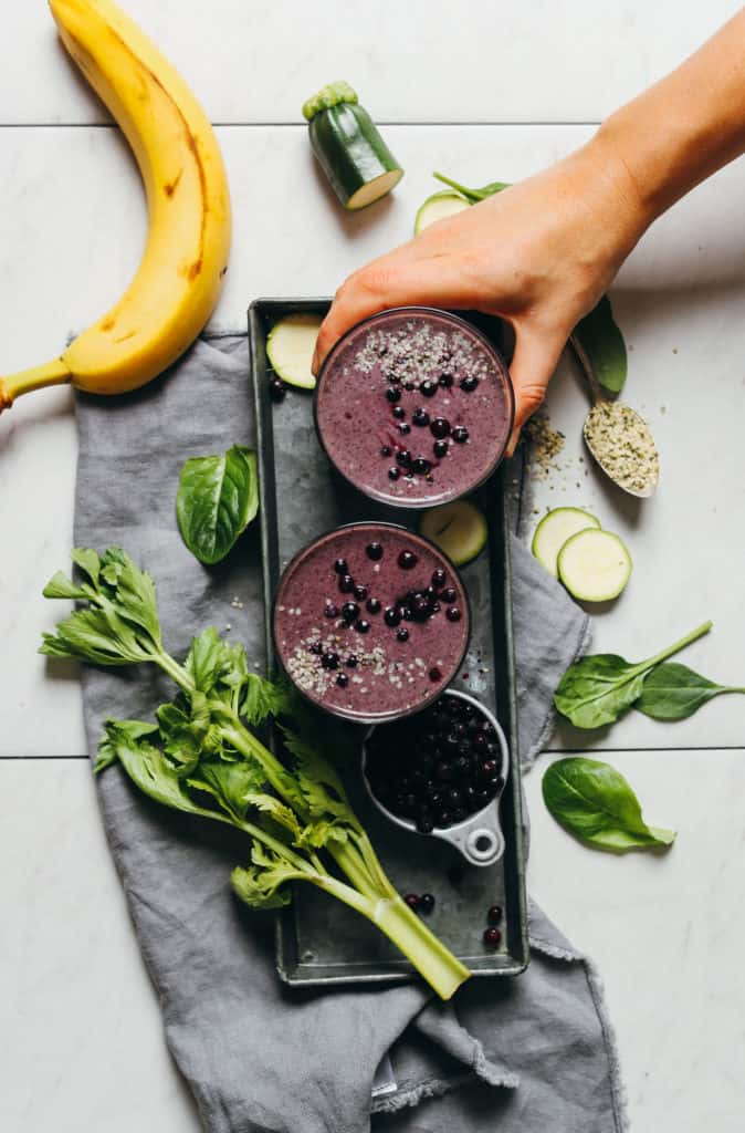 Creamy Blueberry Zucchini Smoothie on a white table with the ingredients around