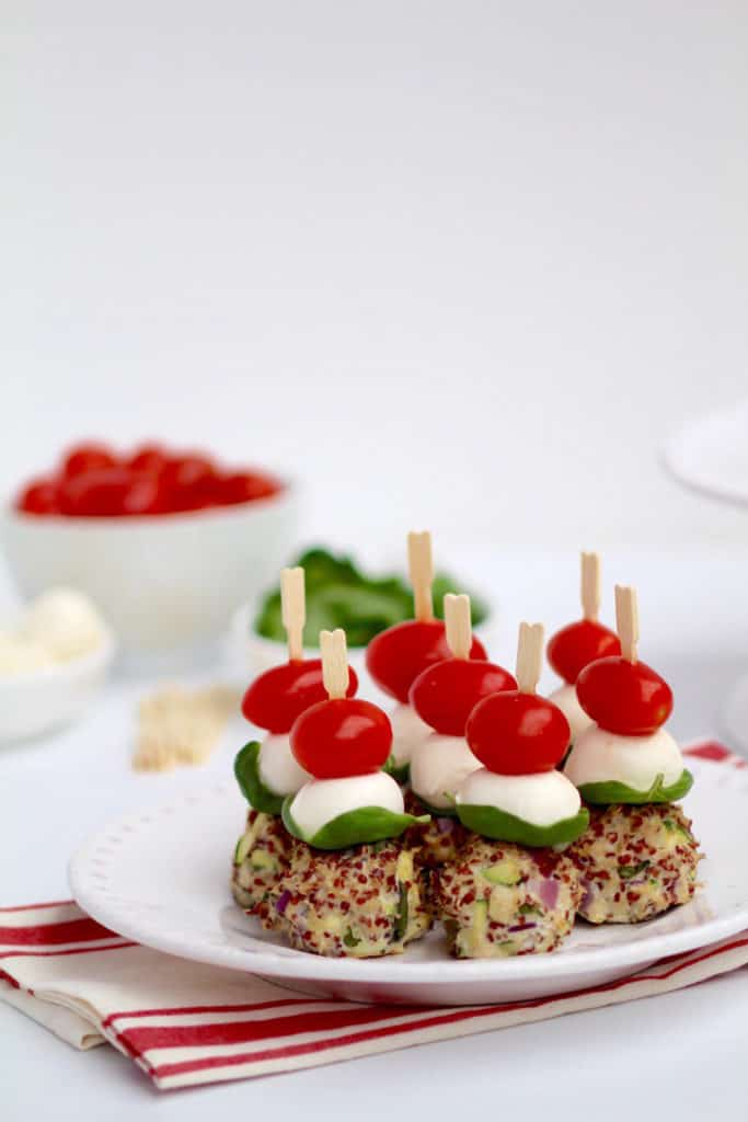 Turkey Meatball Skewers on a white plate with the ingredients in the backgound