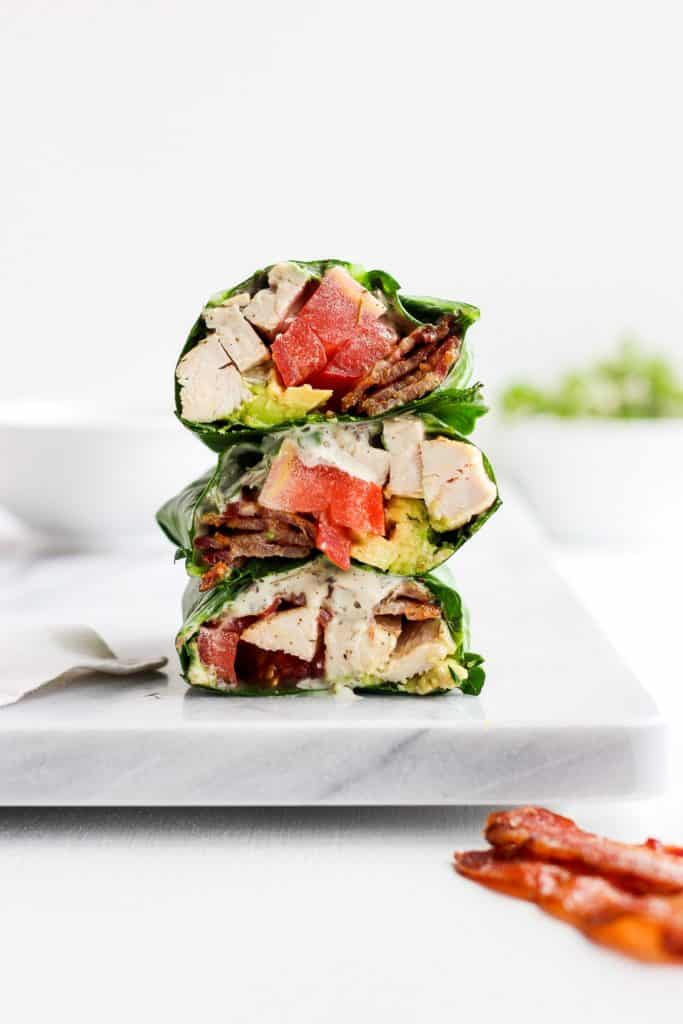 Chicken Bacon Club Collard Green Wraps stacked into threes on a white board