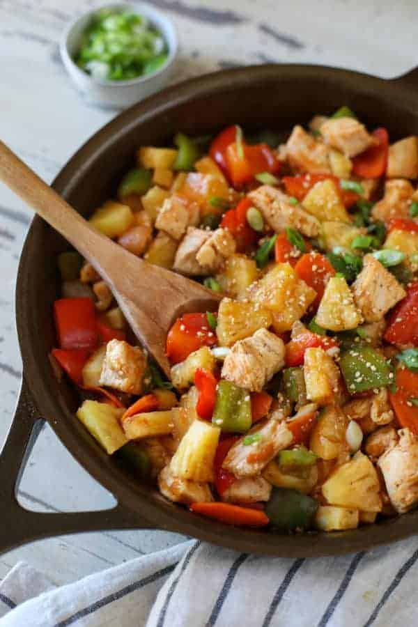 Skillet with wooden spoon scooping into sweet and sour chicken with pineapple and peppers