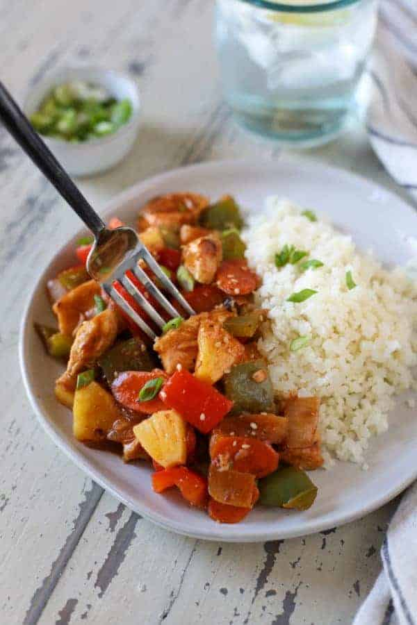 Close up view of Sweet and Sour Chicken with a side of rice on a white plate with a fork