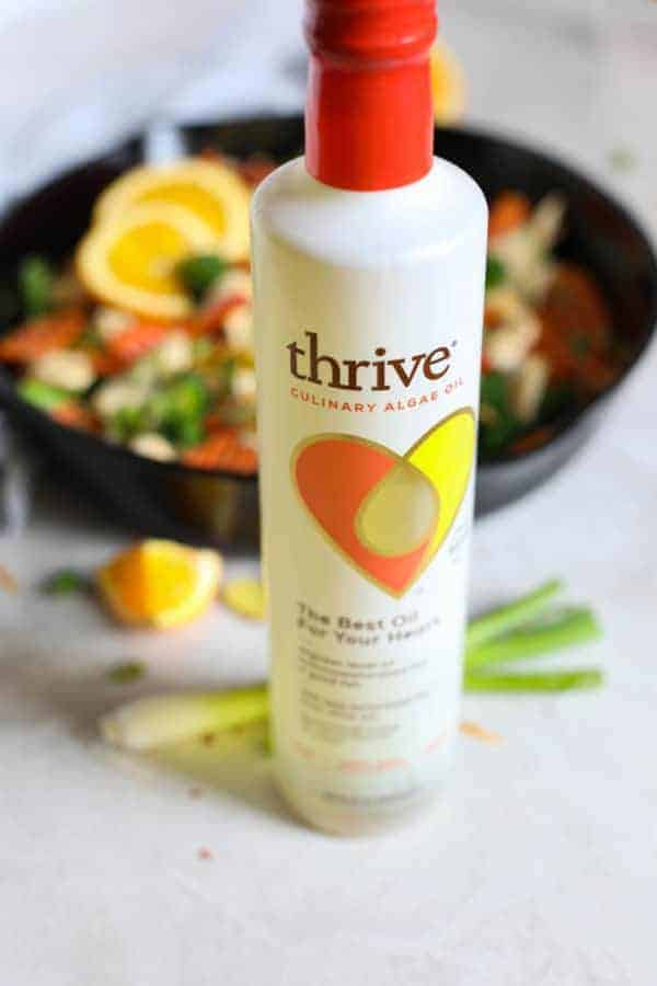 Thrive Culinary Algae Oil in front of a pan of ingredients for Orange-Ginger chicken Stir Fry