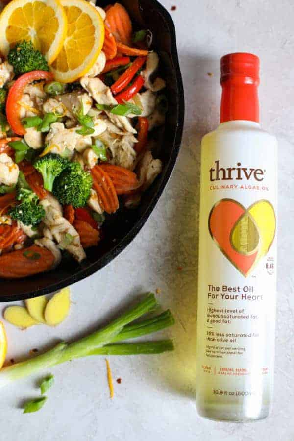 Overhead view of Thrive Culinary Algae Oil next to a pan of ingredients for Orange-Ginger Chicken Stir Fry