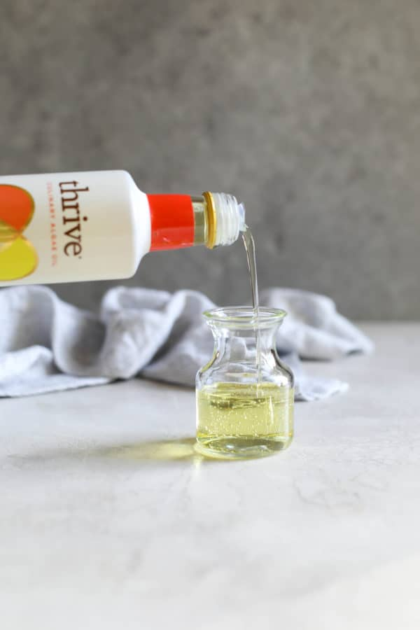 Thrive Culinary Algae Oil being poured into a glass bottle