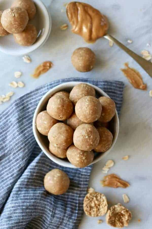 Overhead view of 3-Ingredient Peanut Butter Bites in a white bowl with a spoonful of peanut butter on the side