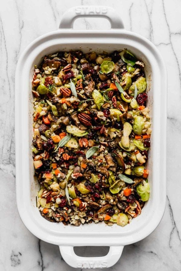 A white baking dish filled with healthy cauliflower stuffing topped with fresh herbs and pecans.