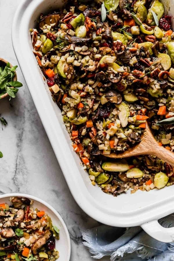 Cauliflower stuffing with brussels sprouts, mushrooms, and pecans in a white baking dish