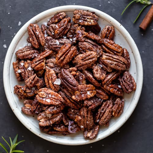 A speckled white plate full of holiday spiced nuts and topped with sea salt flakes