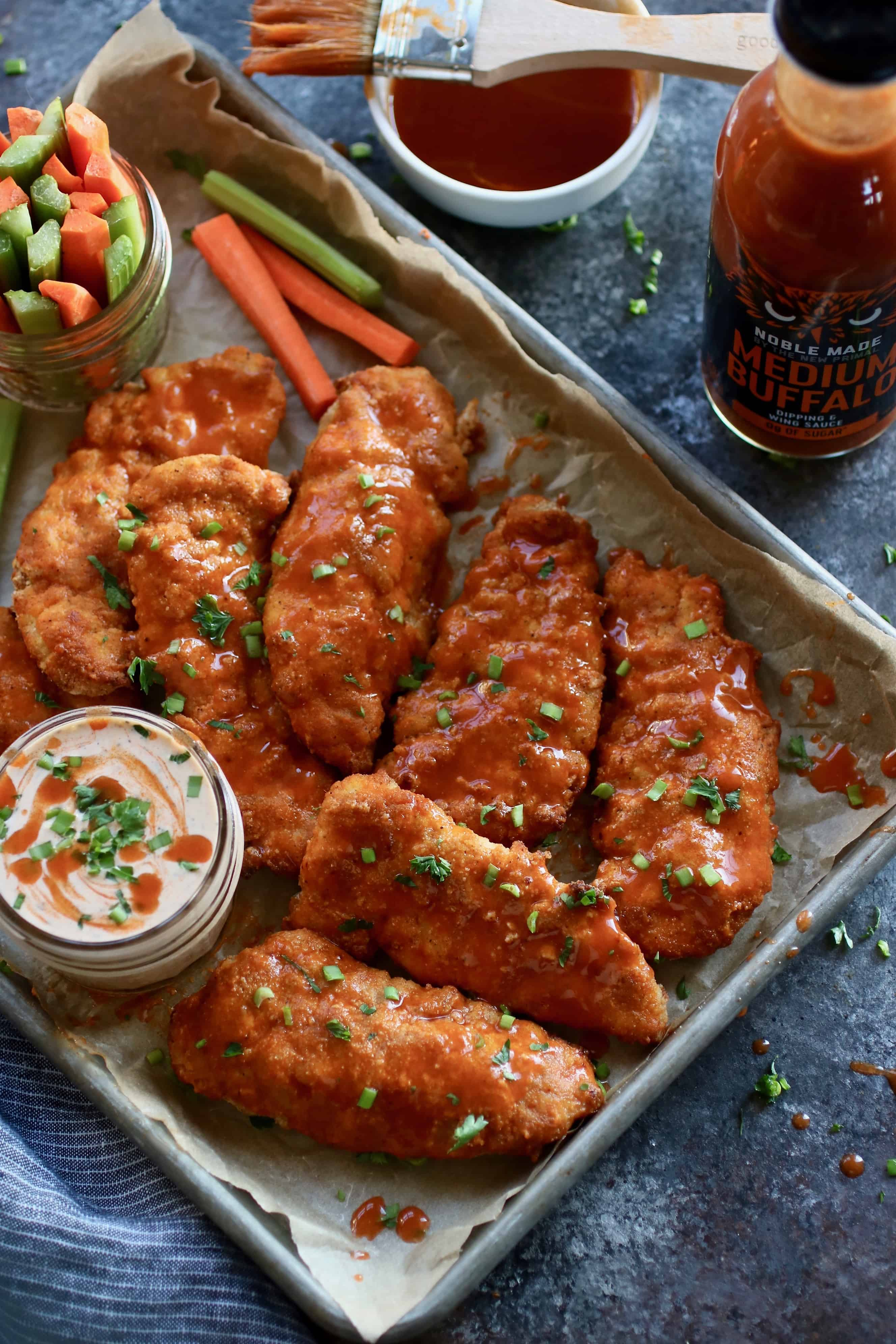 Overhead shot of Buffalo Chicken Strips on a pan with with Buffalo Ranch served in a mason jar as well as carrots and celery served in another mason jar, both are also on the pan.