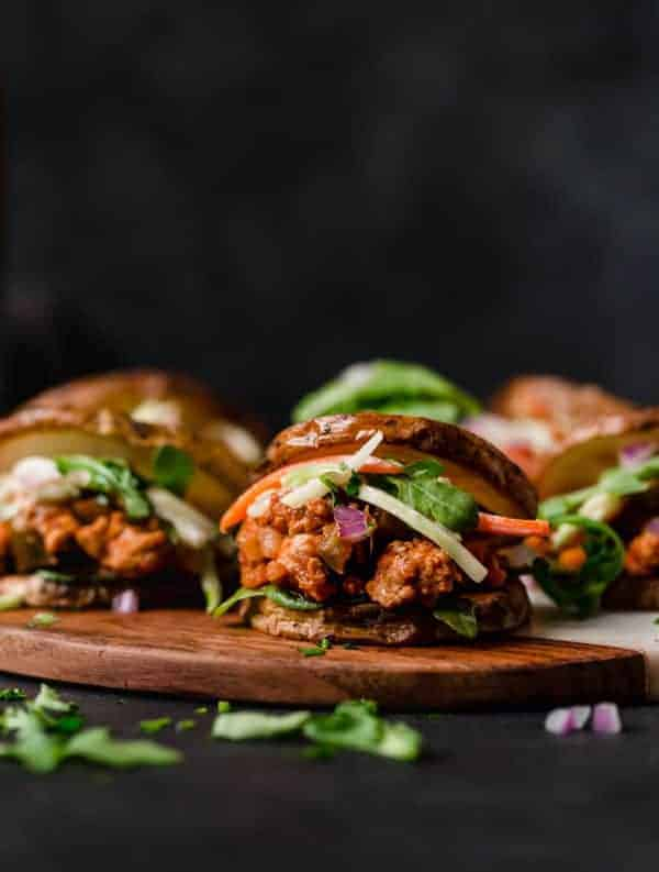 Side view of BBQ Turkey Sloppy Joes on a wooden tray