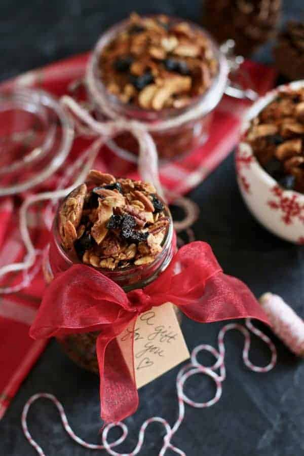 "Vanilla Chai Spiced Granola in a mason jar wrapped with a red ribbon and a tag on it that says ""gift for you""."