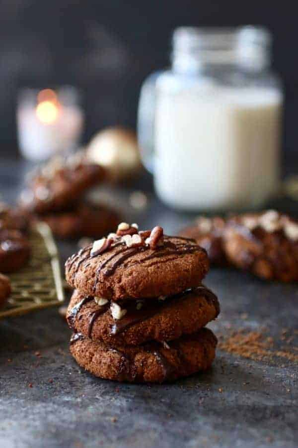 Paleo Soft Batch Ginger Molasses Cookies stacked into a pile of three cookies on a counter top