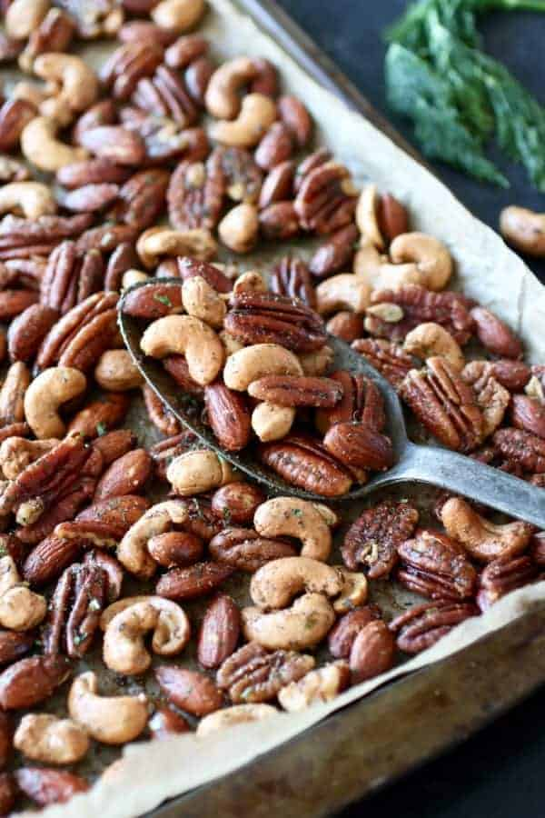 Ranch Roasted Mixed Nuts on a baking pan with a silver spoon holding a scoop of nuts also on the pan.
