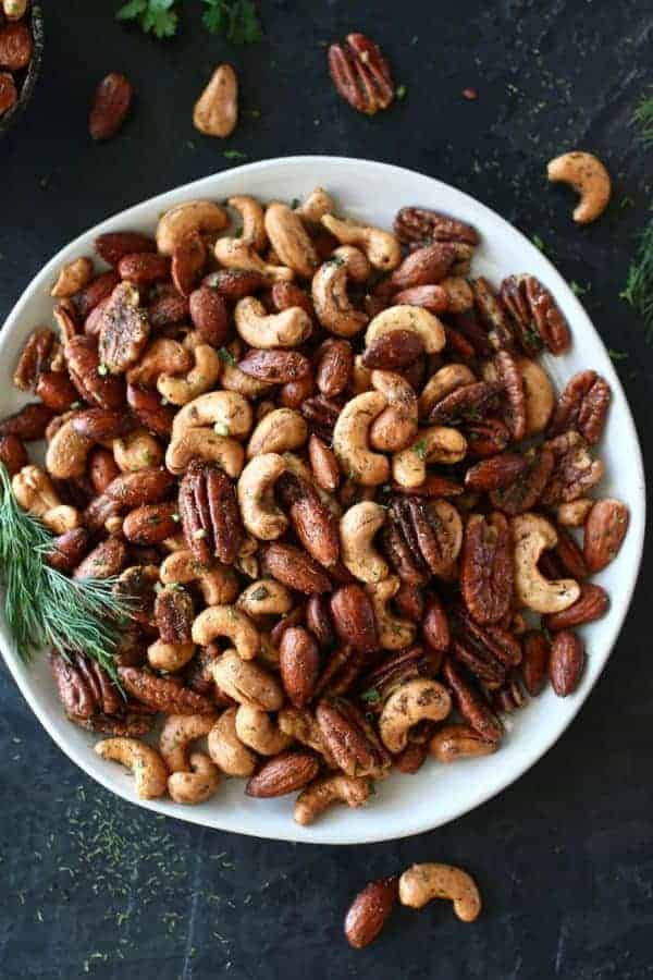 Overhead photo of Ranch Roasted Mixed Nuts on a white plate with dill. Photo taken on a dark background.