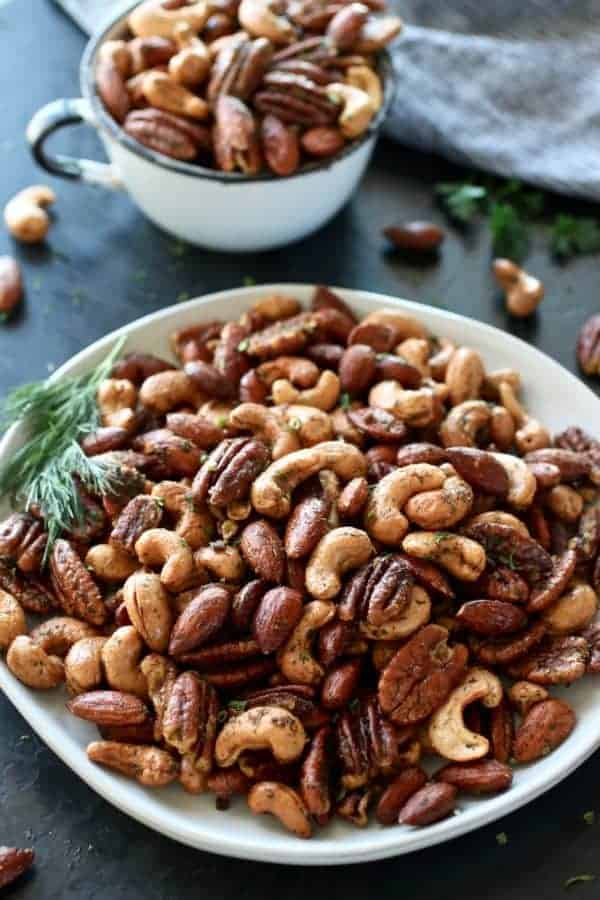 Ranch Roasted Mixed Nuts on a white plate with dill and a cup of mixed nuts in the background. Photo taken on a dark background.