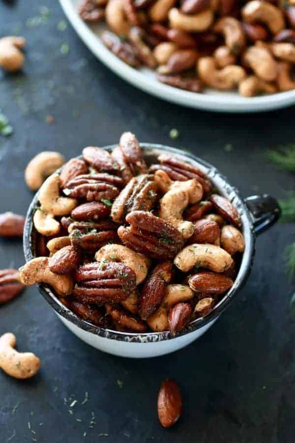 Ranch Roasted Mixed Nuts in a white antique tea cup. Photo taken on a dark background.