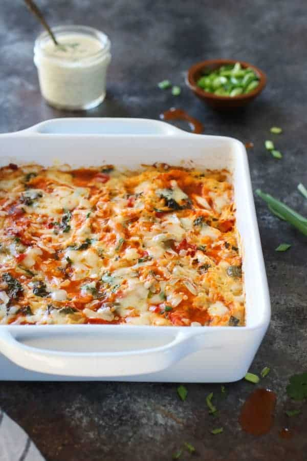 Front angle photo of Buffalo Chicken Bake in a white 9x9 casserole dish with a small mason jar of ranch and small wooden bowl with fresh chives in the background.