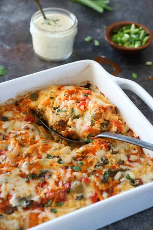 side angel photo of Buffalo Chicken Bake in a 9x9 white dish with a silver spoon holding a scoop. Small mason jar filled with ranch and a small wooden bowl of chives in the background.
