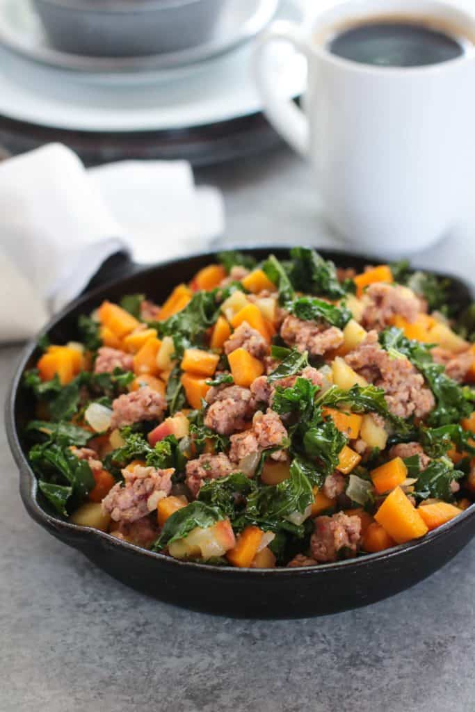 Cast iron skillet filled with Butternut Squash and Apple Hash with Sausage and a cup of black coffee in the background.