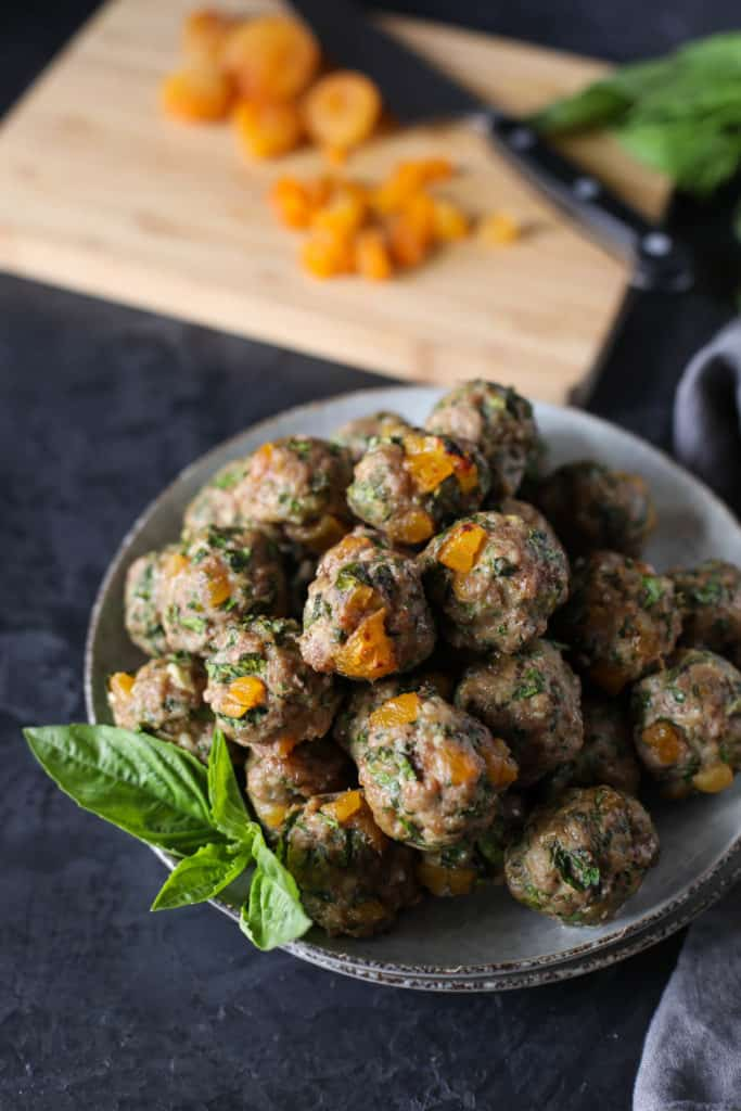 Bowl of Apricot Basil Breakfast Meatballs with a cutting board, knife and dried apricots.
