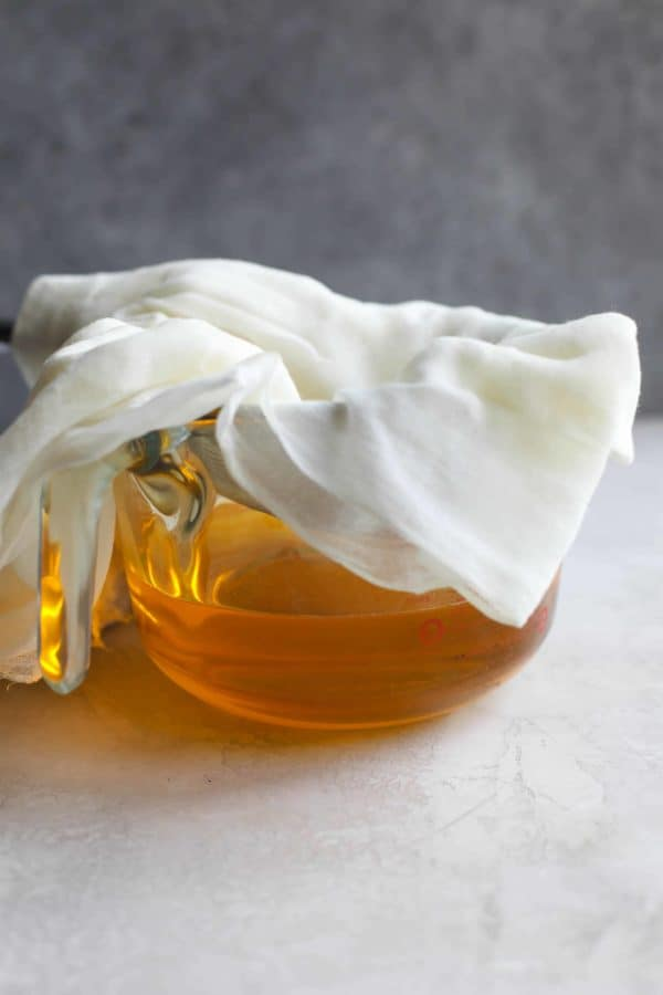 Side view of a bowl of liquid ghee with cheesecloth-lined stainer sitting on top.