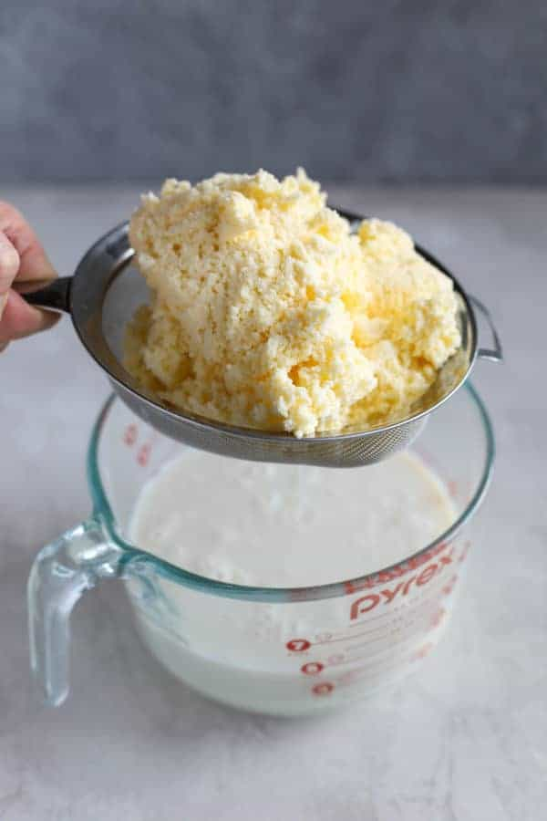 Homemade butter in a strainer. Buttermilk is being strained off.