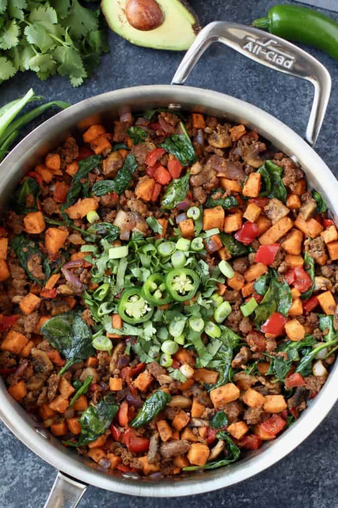 Overhead view of a skillet of Tex Mex Sweet Potato Hash with cilantro and jalapeños on top for garnish.