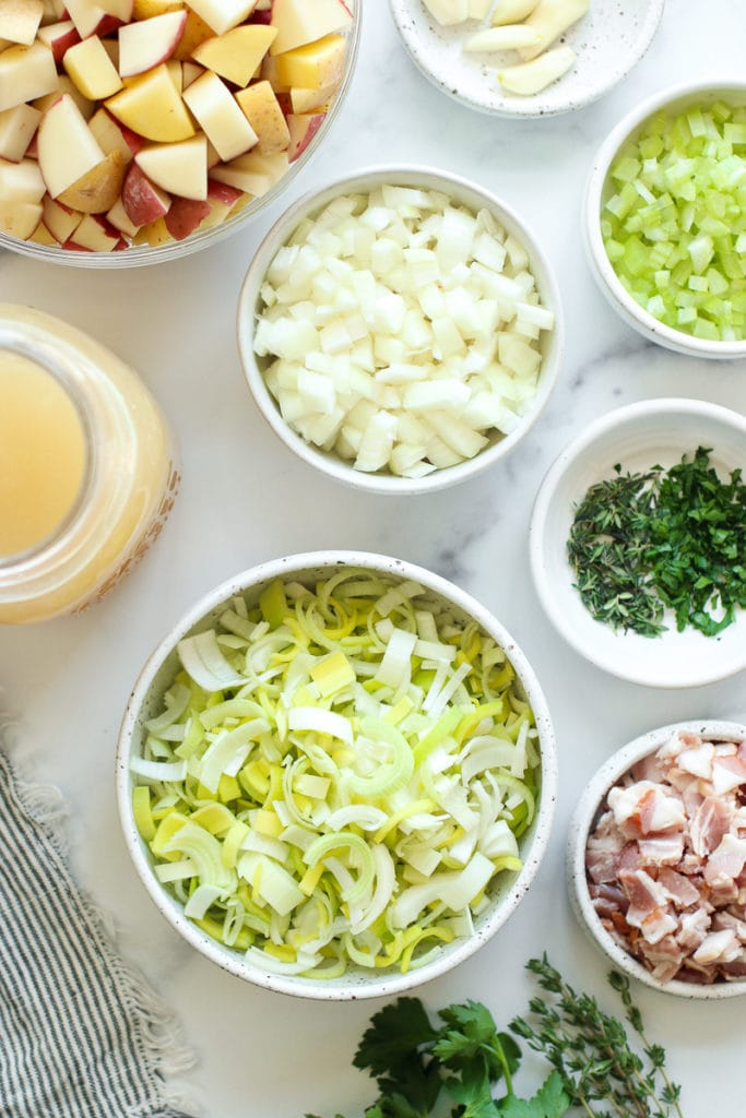 All ingredients for creamy potato leek soup in small bowls and jars.