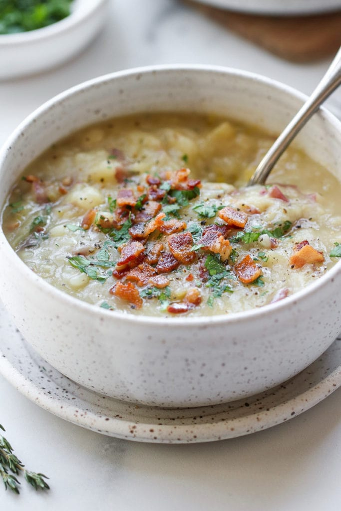 Creamy potato leek soup in a speckled bowl topped with chives and bacon