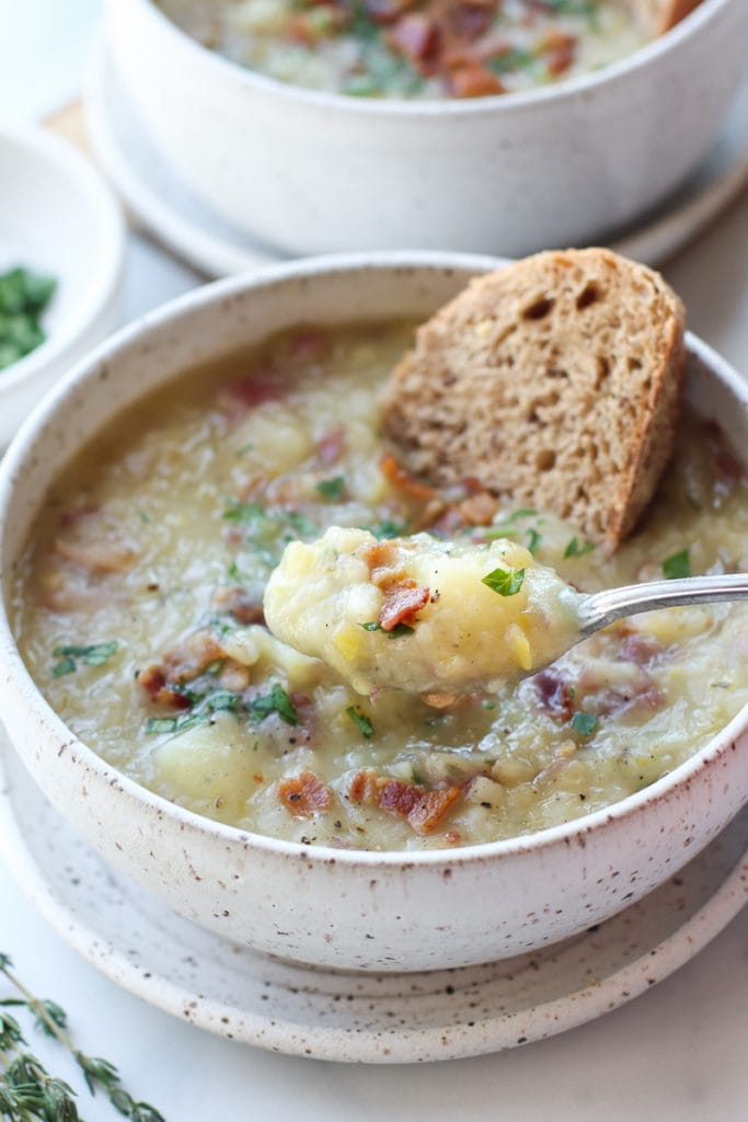 A spoonful of creamy potato leek soup topped with bacon crumbles with crusty bread on the side.
