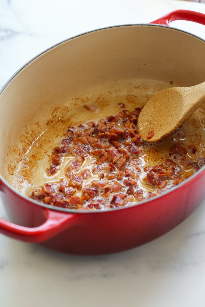 Bacon crumbles cooking in a red pan