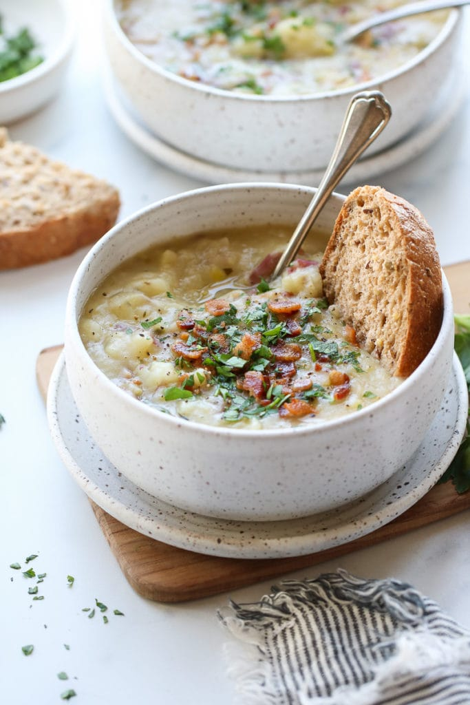 A bowl of creamy potato leek soup topped with bacon with a side of crusty bread