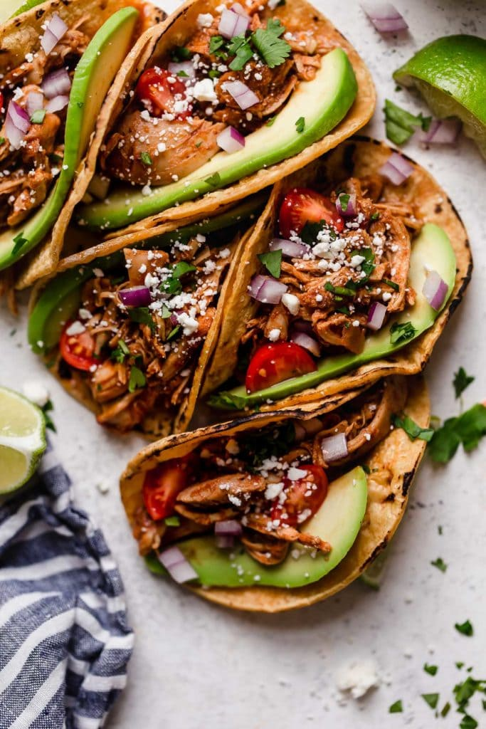 Slow Cooker Chicken Tacos in a corn tortilla with fixings.