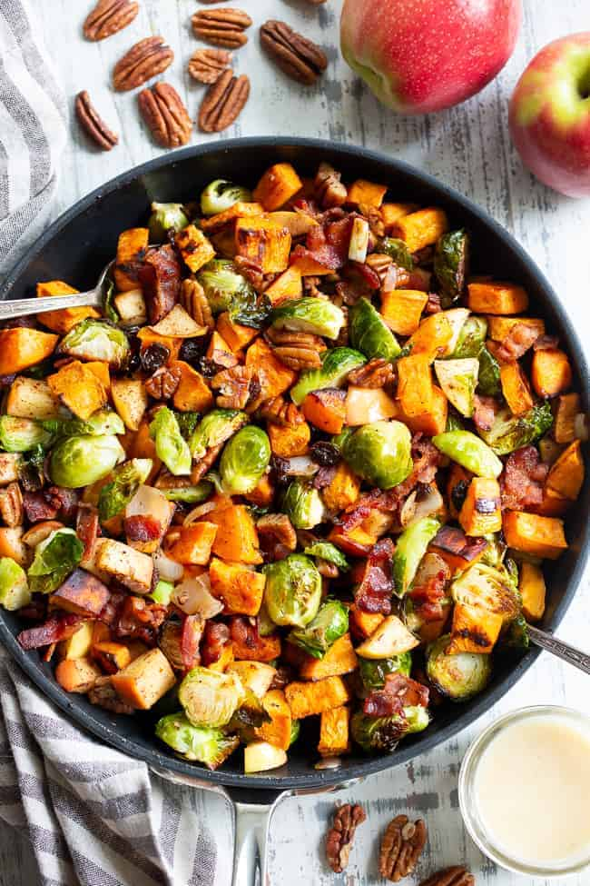 Skillet of Harvest Hash with Bacon and Apple Vinaigrette with pecans and apples next to it.