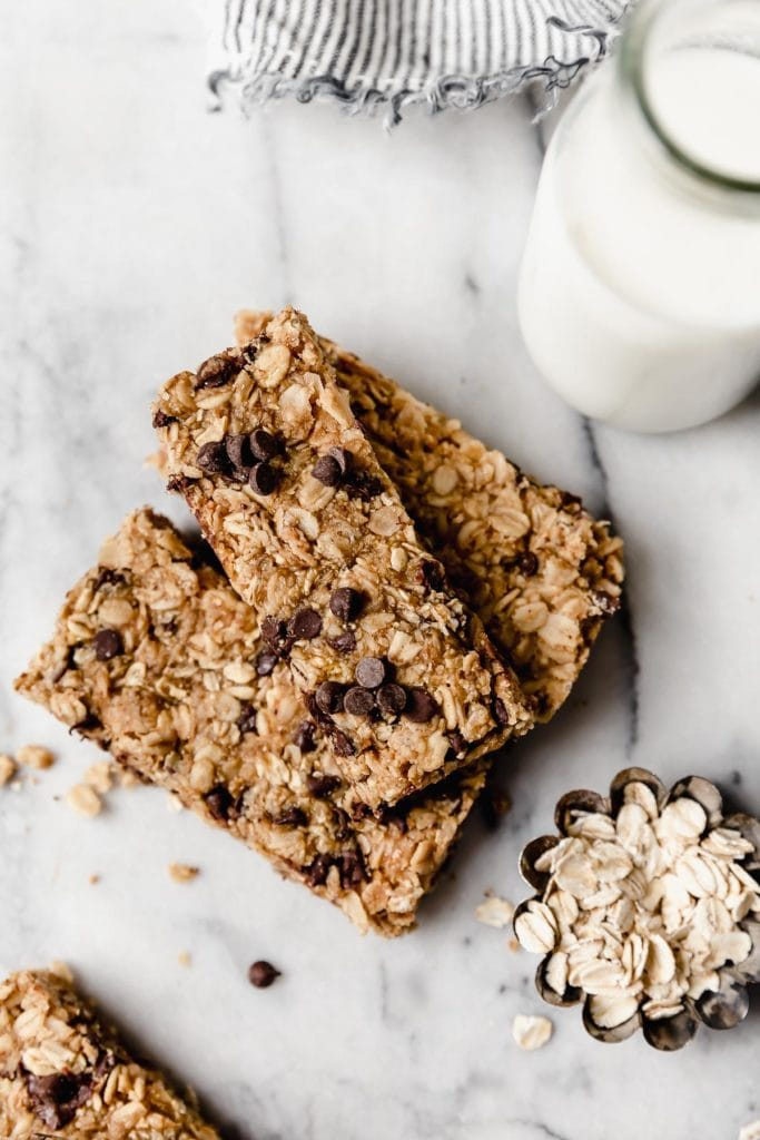 Overhead shot of healthy granola bars, with oats scattered and a glass of milk