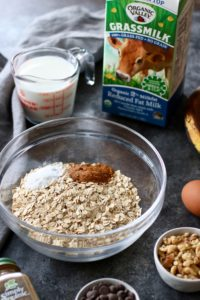 Photo of ingredients needed to make Banana Chocolate Chip Baked Oatmeal including a clear bowl holding oats and spices and 1/2 gallon carton of Organic Valley Grassmilk Milk in the background.