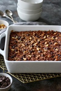 Photo of Banana Chocolate Chip Baked Oatmeal in a 9x9 white dish just out of the oven. Side angle photo.